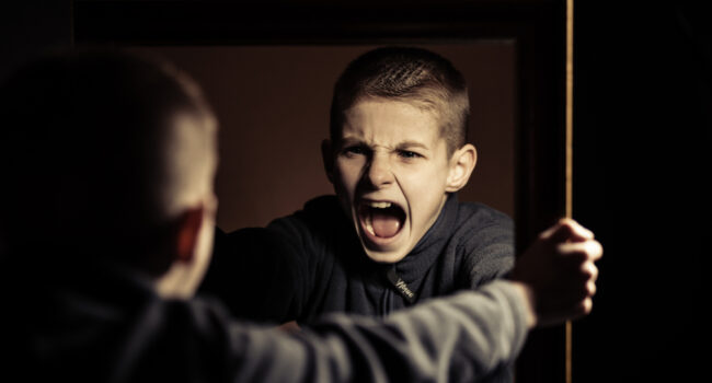 Close,Up,Angry,Young,Boy,Shouting,On,His,Own,Mirror