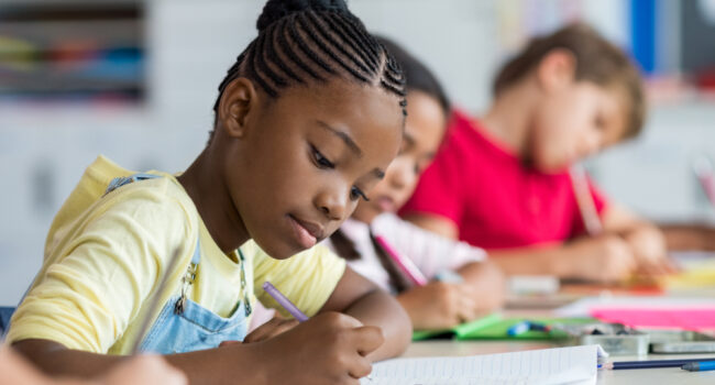 Cute,Pupil,Writing,At,Desk,In,Classroom,At,The,Elementary